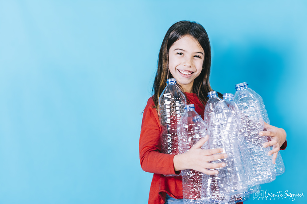 Niña con botellas de plástico